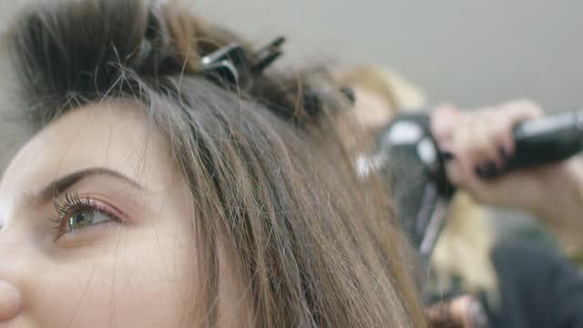 vídeos de stock, filmes e b-roll de fique bonita e ame-se. mude seu visual. jovem mulher milenar em uma boutique de cabeleireiro. close-up em câmera lenta do cabeleireiro aplicando tratamento capilar em cabelos castanhos longos de seu cliente. - brown hair