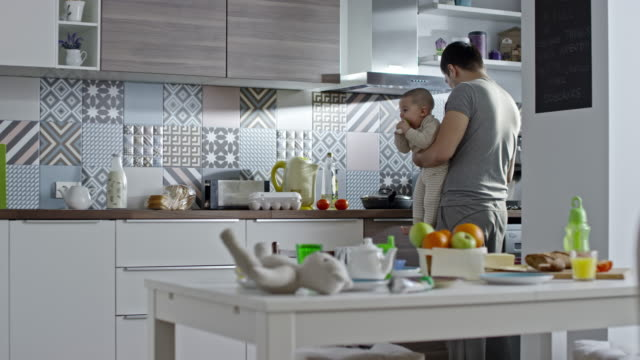 Stay-at-home dad holding baby boy and cooking in kitchen