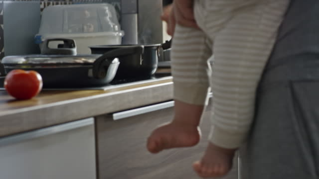 stay-at-home father holding baby and preparing breakfast - 調理鍋点の映像素材/bロール