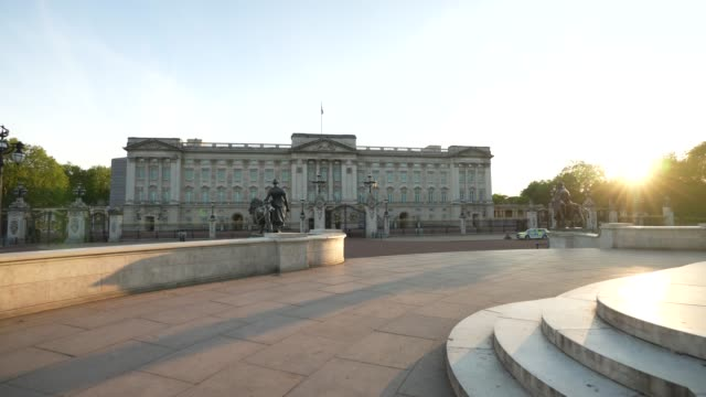 steadicam a police car patrols outside an almost empty buckingham palace at sunset time during the global outbreak of coronavirus covid19 pandemic... - dusk stock videos & royalty-free footage