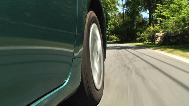 stockvideo's en b-roll-footage met pov steadicam , a wheel spins as a car travels down a wooded lane. / california - autoband
