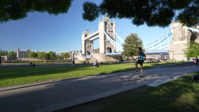 steadicam - members of the public do their daily exercise on bankside next to tower bridge during the global outbreak of coronavirus covid-19... - international landmark stock-videos und b-roll-filmmaterial