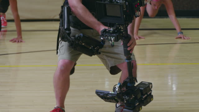 Steadicam Operator and First Camera Assistant shoot a RED camera during a fitness bootcamp; following women exercising in a gym