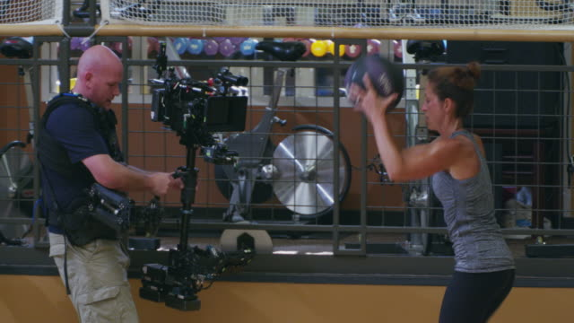 steadicam operator and first camera assistant shoot a red camera during a fitness bootcamp; following women exercising in a gym - military fitness stock videos and b-roll footage