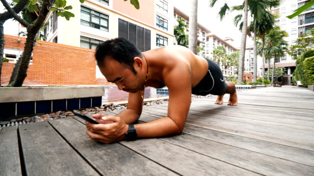 steadicam shot : asian man doing exercise planking and using smart phone at swimming pool. - postura video stock e b–roll