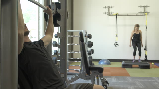 Steadicam shot of a man lifting weights in a gym