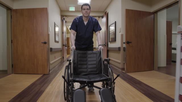 vidéos et rushes de steadicam shot of a nurse pushing a wheelchair down a corridor - infirmier