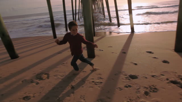 Steadicam tracks children playing under dock
