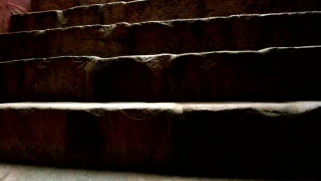 POV steady cam shot of climbing ancient stone stairs to tomb.