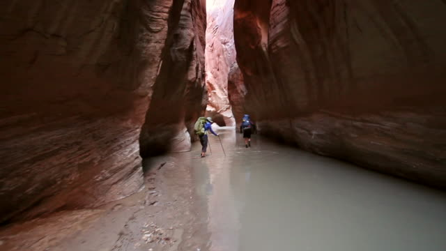 steady cam shot of man and woman hiking with backpacks  through river in deep red rock desert slot canyon. - narrow stock videos & royalty-free footage