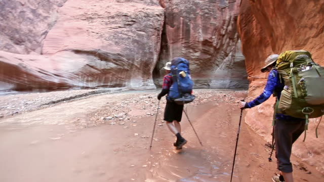 Steady cam shot of man and woman hiking with backpacks  through river in deep red rock desert slot canyon.