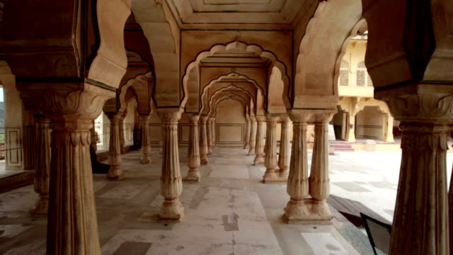 POV steady cam shot of walking through ornately carved archways in ancient stone building.