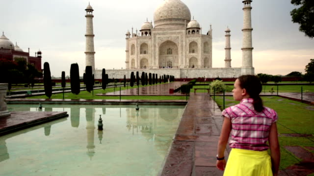 steady cam shot of young girl walking toward taj mahal after rainstorm. - agra stock videos and b-roll footage