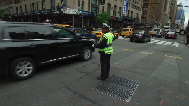 steady cam walking shot of nypd police directing traffic in new york city - directing stock videos & royalty-free footage