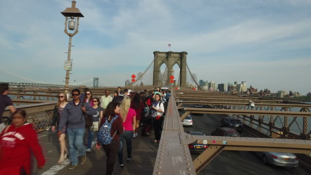 Steady cam walking shot of tourists on top of the Brooklyn bridge