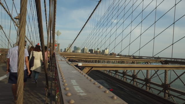Steady cam walking shot of tourists walking on top of the Brooklyn bridge
