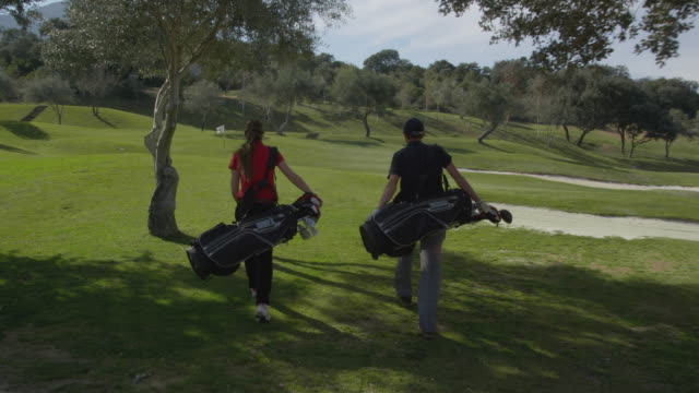 vídeos de stock e filmes b-roll de ts (steadycam) camera follows two young golfers, male and female, as they approach a green, set their bags down, go onto the green and study the position of their golf balls, red r3d 4k - golfe