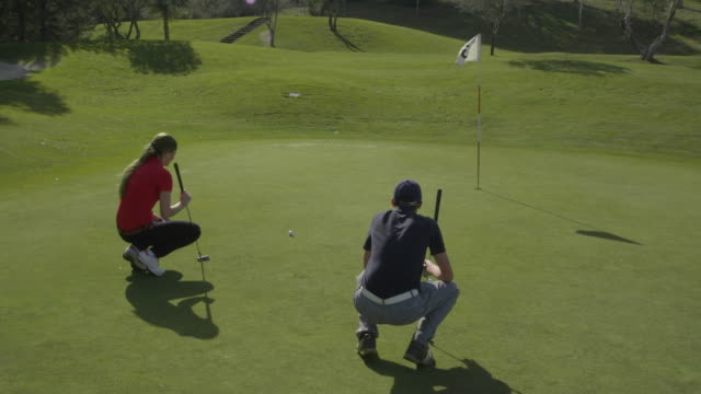 TS (steadycam) camera follows two young golfers, male and female, as they set their bags down on the side of the green, go onto the green and study the position of their golf balls, man plays his ball, misses the hole, RED R3D 4K