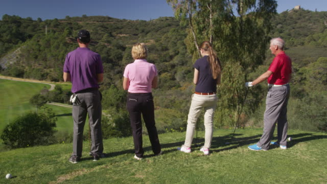 ts ms (steadycam) four golfers (young and mature couples) standing on tee looking out over fairway ahead, red r3d 4k - golf glove stock videos and b-roll footage