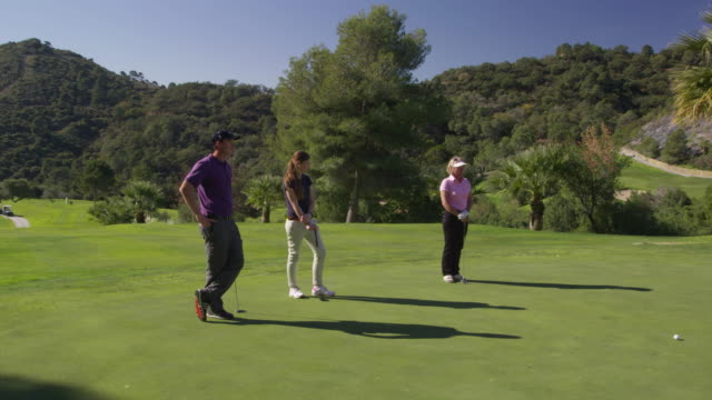 ds ws (steadycam) three golfers (one man, two women) standing on green, one woman approaches ball and putts red r3d 4k - golf glove stock videos and b-roll footage
