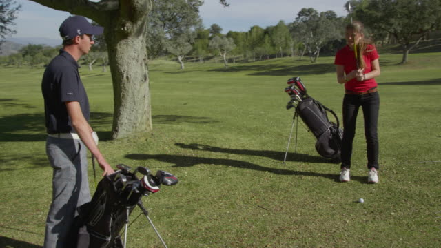 ds (steadycam) two young golfers, male and female, on fairway, doing practice swings; camera moves around them and man plays ball, red r3d 4k - golf glove stock videos and b-roll footage