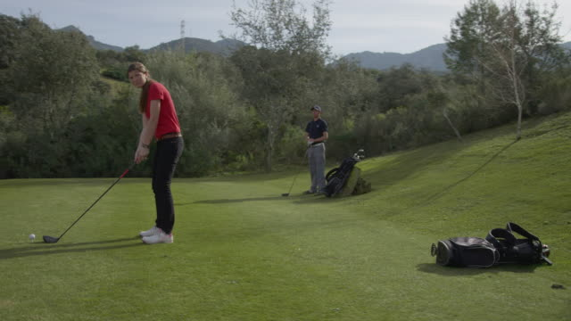 ds (steadycam) varispeed shot; young female golfer on tee, camera moves from front to side in real time, then captures swing in slo-mo, red r3d 4k - golf shot stock videos & royalty-free footage