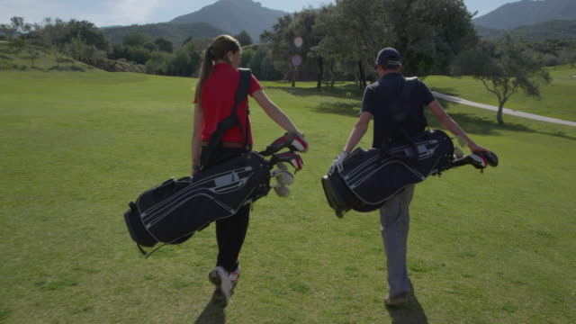 pov ds (steadycam) young man and woman golfer walking on fairway, camera approaches from front, passes them, turns and follows them as they walk, red r3d 4k - golfer stock videos and b-roll footage