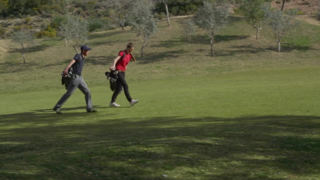 TS (steadycam) young man and woman golfer walking on fairway, camera tracks in parallel through trees, finally passes them, turns and they drop their bags and talk, RED R3D 4K