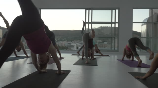 ws steadycam_big yoga class exercising in rooftop studio - sun salutation stock videos and b-roll footage