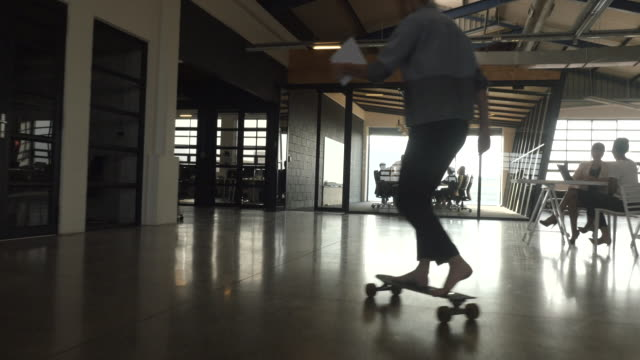 Steady-cam_Businesswoman rolling into meeting on a skateboard