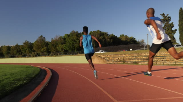 ws steadycam_camera following male track athlete sprinting on track - running shorts stock videos & royalty-free footage