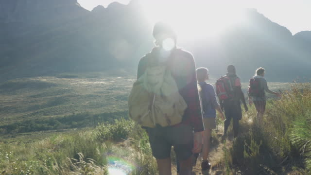 steady-cam_group of friends hiking on path threw mountain area, at sunrise - 20 29 years stock videos & royalty-free footage
