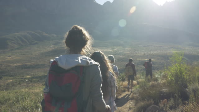 STEADY-CAM_Group of friends hiking on path threw mountain area, at sunrise