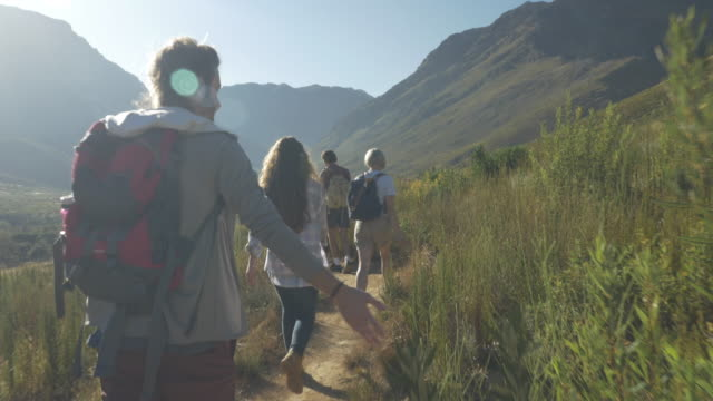 vídeos de stock e filmes b-roll de steady-cam_group of friends hiking on path threw mountain area, at sunrise - acampar