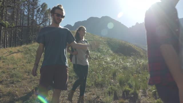 vídeos y material grabado en eventos de stock de steady-cam_group of friends hiking on path threw mountain area, at sunrise - mochila bolsa