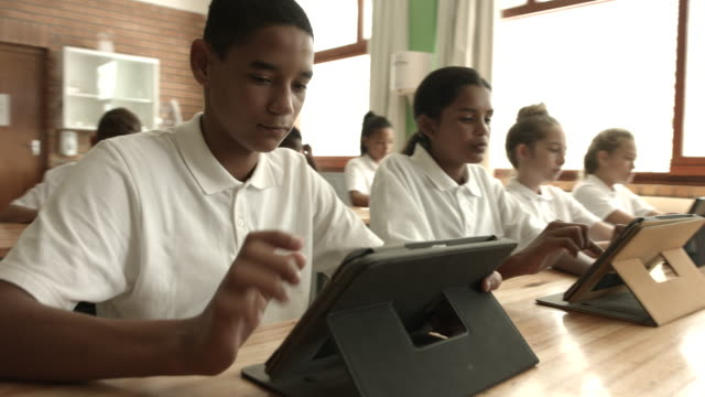 vídeos de stock, filmes e b-roll de ms steadycam_schoolkids working on digital tablets in classroom - adolescência