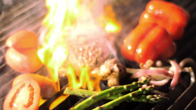 Steak and vegetables sizzle on a grill.