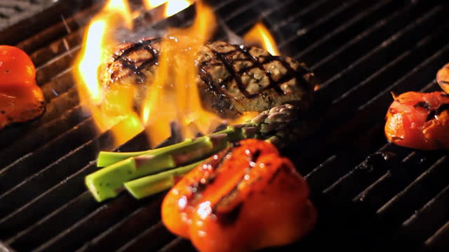 A steak gets placed on a fiery grill.