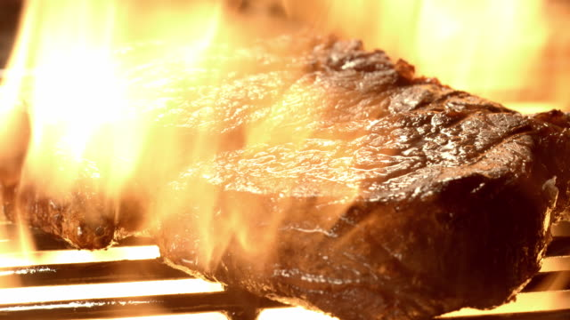 CU steak on open flame grill with  flames shooting up on all sides of meat