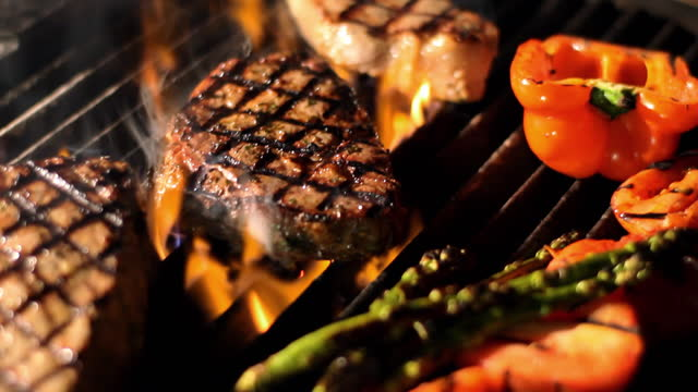 Steaks and vegetables sizzle on a grill.