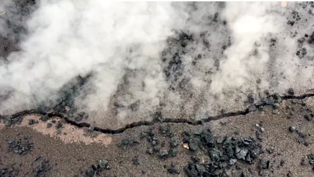 steam and volcanic gases escape from a crack in the roadway in the leilani estates neighborhood in the aftermath of eruptions from the kilauea... - lava stock videos & royalty-free footage