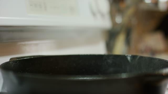 stockvideo's en b-roll-footage met stoom andsmoke stijgt van een gietijzeren koekepan op een reeks brander - braadpan