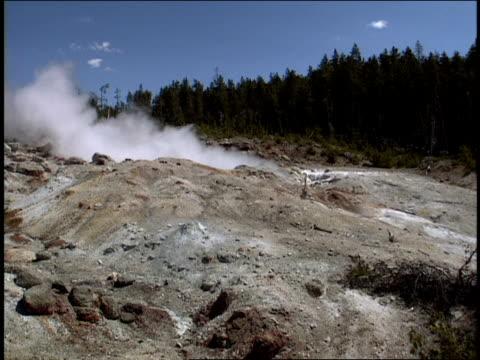 steam billows across rocky terrain at yellowstone national park. - 水の形態点の映像素材/bロール