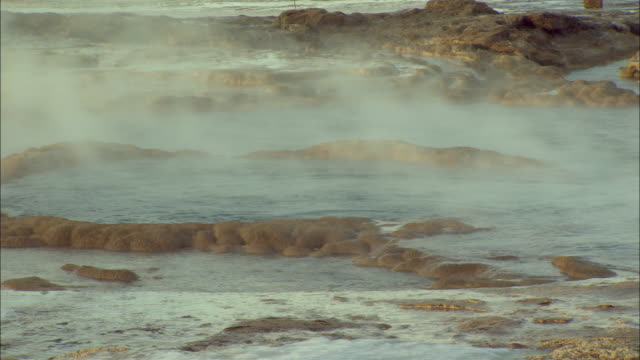 steam billows out of a crevice as a geyser suddenly erupts blasting boiling water and steam outward. - crevice stock videos & royalty-free footage