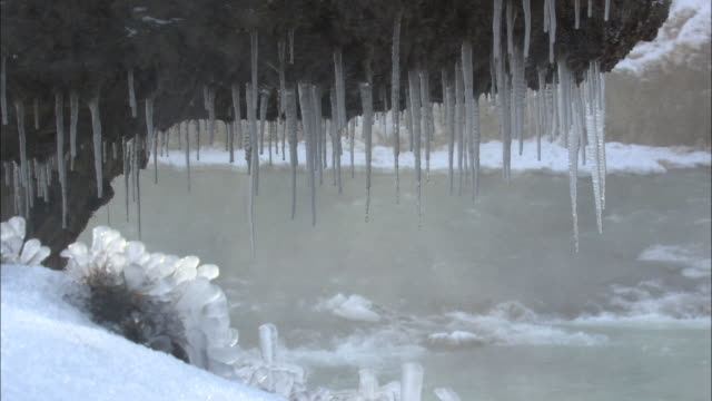 steam blows past icicles hanging from a rock at gullfoss waterfall in iceland. - falling water stock videos & royalty-free footage