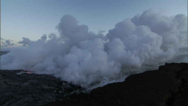 steam clouds billow from the shore as burning lava flows into the sea. - pazifik stock-videos und b-roll-filmmaterial