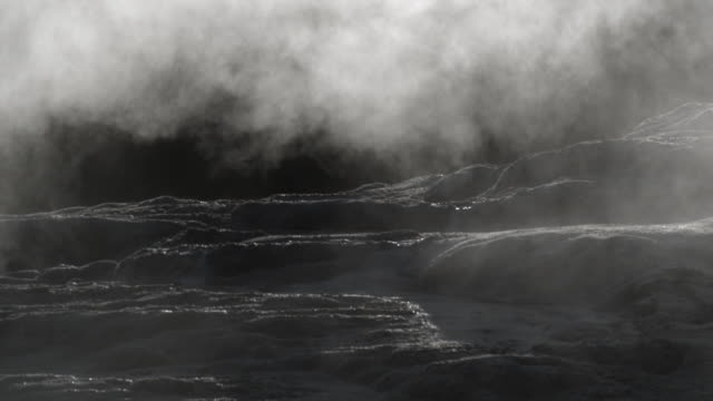 steam drifts over mineralised rocks near geyser. - old faithful stock videos & royalty-free footage