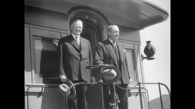 vidéos et rushes de steam engine moves towards camera / herbert hoover on back of train with another man / hoover alights from train shakes hands and smiles at waiting... - 1933