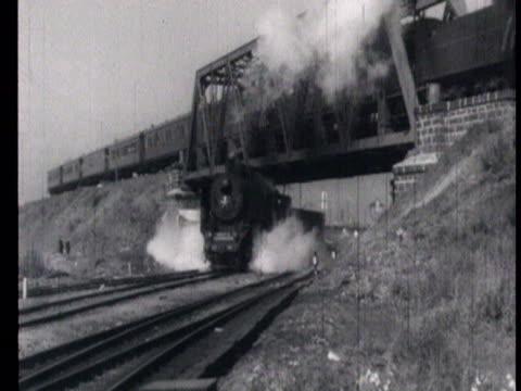 steam engine passing under bridge and another train going over bridge while conductors along train tracks signaling, steam train comes into train... - anno 1951 video stock e b–roll