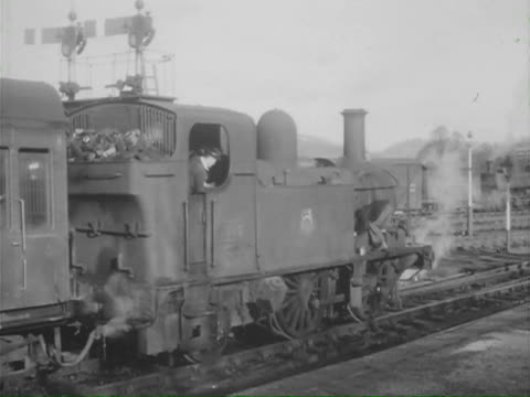 vidéos et rushes de ms pan ts steam engine pulling into station and people on platform  and station master ringing bell, old passenger carriage wooden benches / various,various,france - locomotive